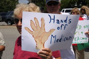 An old woman holding up a sign that says hands off medicare
