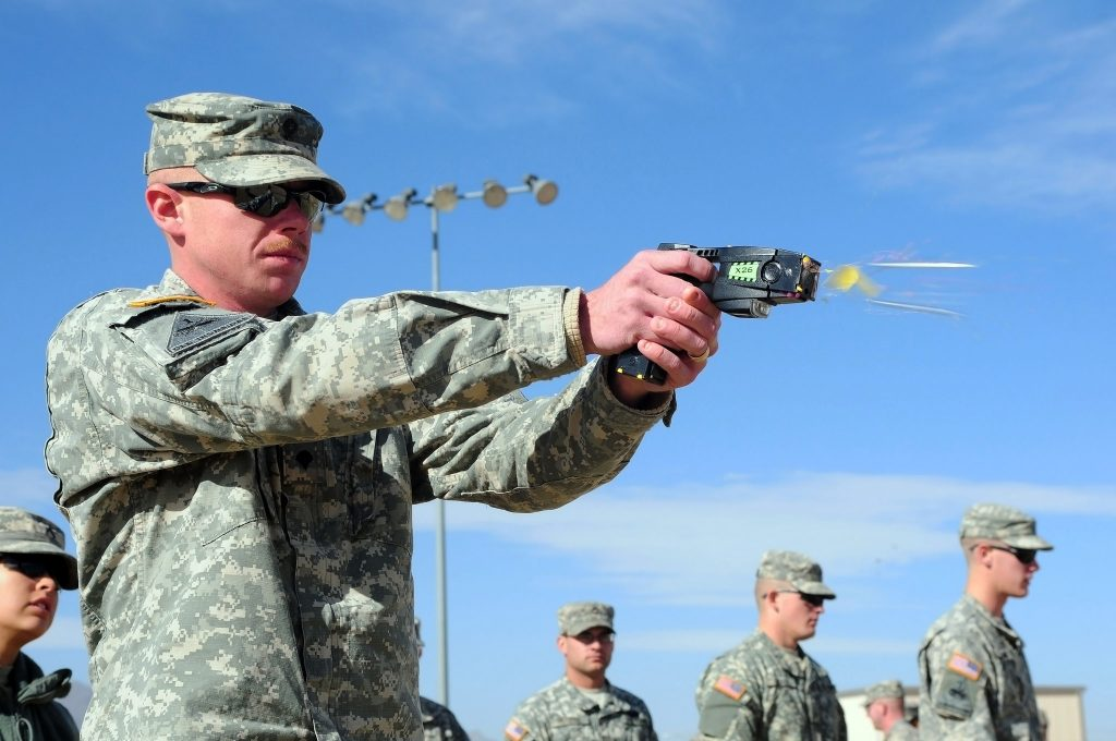 A person in military fatigues demonstrating a taser